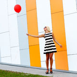Girl with balloon. Happy young beautiful woman standing with colorful latex balloon. On the background an orange colored wall. Outdoors, lifestyle Stock Photo