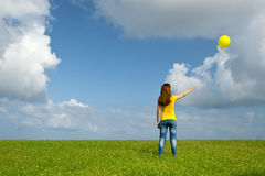 Girl with a balloon. Happy young woman with a yellow balloon on a green meadow stock photos