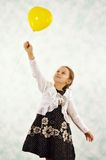 Girl and balloon. Girl holds in a hand yellow balloon in the shape of heart. Imitation of an older snapshot Royalty Free Stock Photos