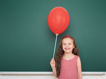 Girl with balloon near school board Stock Photo