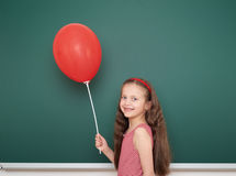 Girl with balloon near school board Royalty Free Stock Image