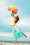 Girl with balloons. Happy girl holding bunch of colorful air balloons at the beach Royalty Free Stock Photo