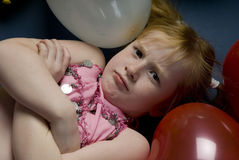 Girl between balloons. Young girl is laying down between balloons Royalty Free Stock Photos