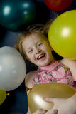 Girl between balloons. Young girl is laying down between balloons Royalty Free Stock Image
