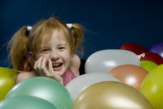 Girl between balloons. Young girl is laying down between balloons Stock Image
