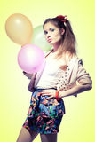 Girl with balloons. Pretty girl with a pony tail holding balloons on yellow background Royalty Free Stock Images