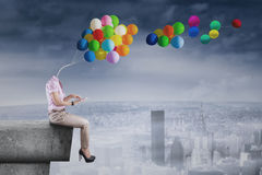 Girl with balloons head using tablet Royalty Free Stock Images