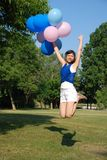 Girl with balloons jumping Royalty Free Stock Photo