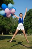 Girl with balloons jumping Royalty Free Stock Image