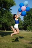 Girl with balloons jumping Royalty Free Stock Photography