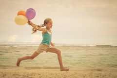 Girl with balloons  jumping on the beach Royalty Free Stock Photos