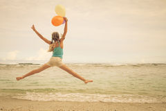Girl with balloons  jumping on the beach Royalty Free Stock Photography