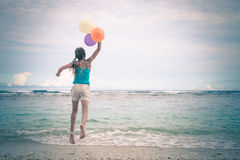 Girl with balloons  jumping on the beach Royalty Free Stock Photo