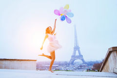 Girl with balloons jumping near Eiffel Tower in Paris Royalty Free Stock Photo