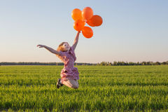 Girl with balloons jumping Stock Photo