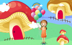 A girl with balloons near the mushroom houses Royalty Free Stock Photography