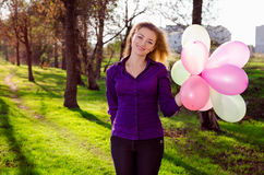 Girl with balloons. In the park stock images