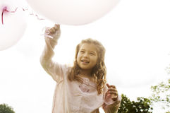 Girl with balloons in park. Stock Photos
