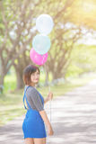 The girl with balloons plays on the road Stock Image