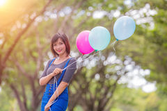 The girl with balloons plays on the road Stock Photos