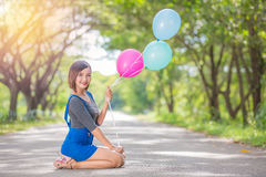 The girl with balloons plays on the road Stock Photo