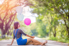 The girl with balloons plays on the road Royalty Free Stock Photo