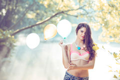Girl with balloons posing at river bank in morning stock photos