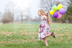 Girl with balloons running Stock Photos