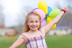 Girl with balloons running Stock Photography