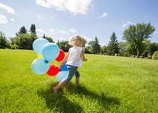 Girl With Balloons Running In Meadow Royalty Free Stock Image