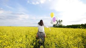 Girl with balloons on the shoulders of the guy runing in field. Rape stock footage