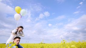 Girl with balloons on the shoulders of the guy runing in field. Rape stock video footage