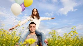Girl with balloons on the shoulders of the guy runing in field. Rape stock video