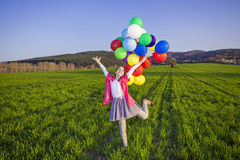 Girl with balloons. Teenage girl with balloons in green field Stock Images
