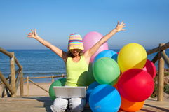 Girl with balloons using a laptop. Happy girl with a bunch of colored balloons using a laptop on the beach royalty free stock photos