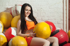 Girl with balls. Beautiful young girl with colored sports balls in the gym Stock Photos