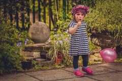 Girl with baloon and lollipop. Little girl with painted face holding her baloon and eating lollipop in the park Royalty Free Stock Photography