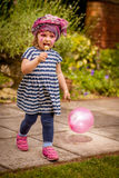 Girl with baloon and lollipop. Little girl with painted face holding her baloon and eating lollipop in the park Stock Photos
