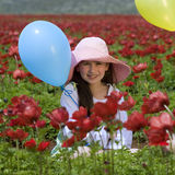 Girl baloon red flowers. Young girl with a hat and blue balloon in a red flowers field Royalty Free Stock Photo