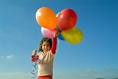 Girl and baloons. Girl holding balloons against blue sky Stock Image