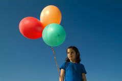 Girl and baloons. Girl holding balloons against blue sky Stock Images