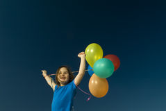 Girl and baloons. Girl holding balloons against blue sky Stock Photo