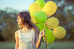 Girl with baloons. Young beautiful girl with baloons in the field stock photos