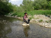 A girl with a banjo sitting on a rock. royalty free stock images
