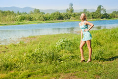 The girl on the bank of the river Royalty Free Stock Photo