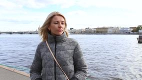 Girl on the bank of the river. Standing and looking into the distance. at the end of the video the girl sends an air kiss stock footage