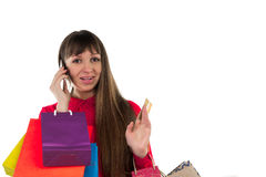 Girl with banking credit card, colorful shopping paper bags, pho. Young woman with banking credit card, colourful shopping paper bags and packages, smartphone Stock Photography