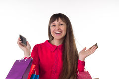 Girl with banking credit card, colourful shopping paper bags, sm. Young woman with banking credit card, colourful shopping paper bags and packages, smartphone Stock Photography