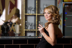Girl at the bar with a glass of champagne Stock Photography