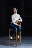 Girl on a bar stool. Girl in a hat sitting on a bar stool Stock Photos